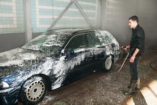 manual car washing cleaning with foam and water at service station