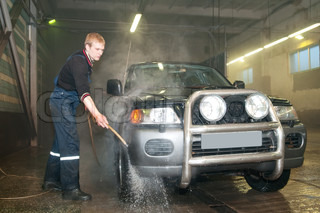manual car washing cleaning with compressed water at service station
