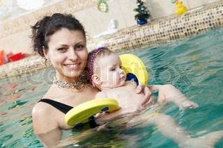happy smiling little girl with mother swimming at water pool