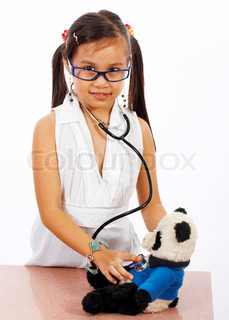 Young Girl Role Playing At Being A Doctor And Checking The Health Of Her Teddy