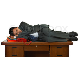 Tired Businessman Having A Sleep On A Desk In His Office