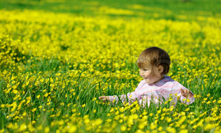 Cute child play on the yellow meadow