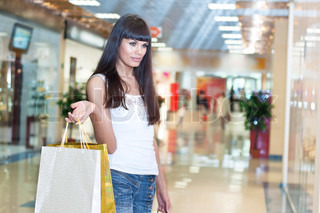 young woman in mall buying clothes, Payment of purchase by a plastic card
