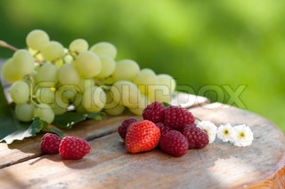 Grapes, strawberries and raspberries on wood table