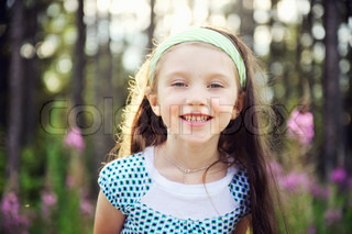 Outdoors portrait of adorable smiling blue-eyed child girl