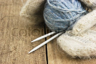 balls of yarn and mittens on a wooden background