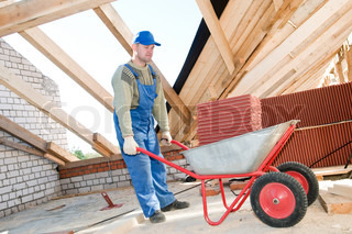 Roofer worker distibuting red clay tiling in wheel barrow at roof