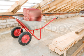 professional galvanized wheelbarrow loaded with reg clay tile at roofing works area