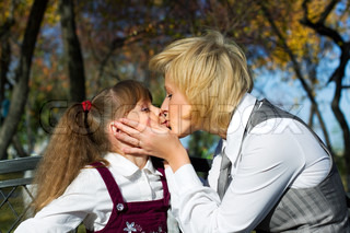 Mother and daughter kissing in autumn park