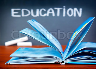 Education concept, open book on the desk in the classroom, chalkboard with education word, back to school