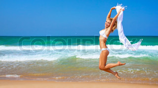 Jumping happy girl on the beach, fit sporty healthy sexy body in bikini, woman enjoys wind, freedom, vacation, summertime fun concept