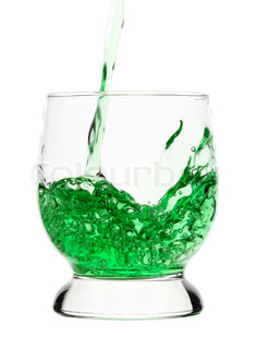 Green drink is being poured into glass, isolated over white