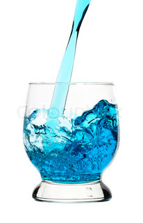 Blue drink is being poured into glass, isolated over white