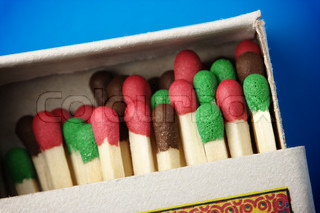 Multicolored matchsticks in the box on blue background, shallow DOF