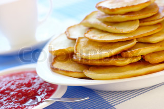 Fresh small pancakes with raspberry jam - traditional Russian cuisine