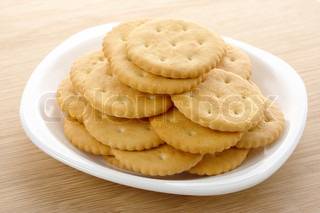 Fresh yellow round crackers on white plate