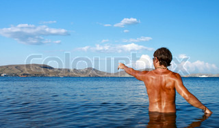 Seminude handsome man standing in the sea with mountains on the background