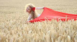 Young attractive woman with the red flower in hair on the wheat field with the red wrap