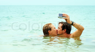 Man kissing the girl and taking the picture of themself in the sea
