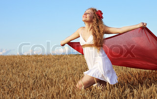 Young woman running on the wheat field with the red wrap