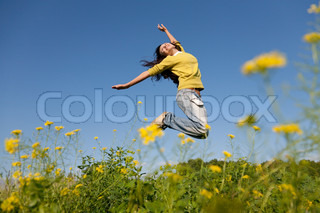 Happy and beatiful young girl jumping high in a summer field