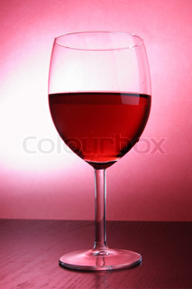 Footed glass of wine over red background