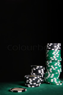 Stacks of casino chips over black background with space for your own text on top