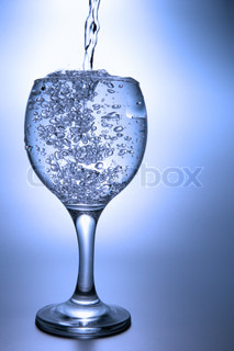 Clear liquid pour into footed glass over blue background
