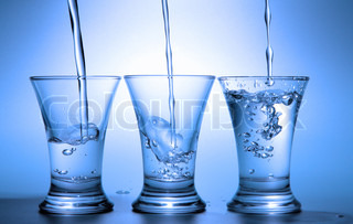 Clear liquid pour into three wineglasses toned in blue color