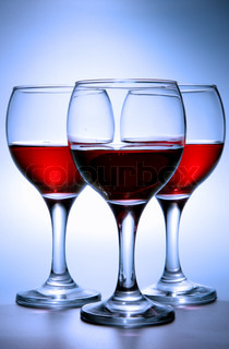 Still-life with three glasses of red wine over blue background