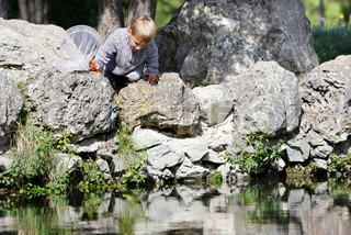 young boy sitting on rocks and looking into water