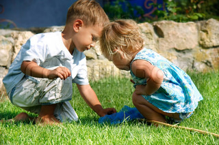 brother and sister playing in green grass