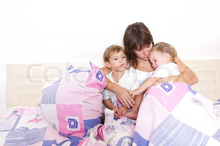 mother and two kids in bed