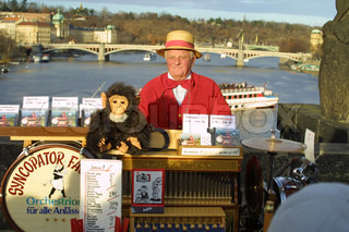 PRAGUE - JANUARY 1, 2007: Famous street organ performer in traditional Czech clothes entertaining visitors at Charles Bridge on January 1, 2007 in Prague, Czech Republic