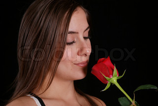 Young woman smelling a red rose on a black background