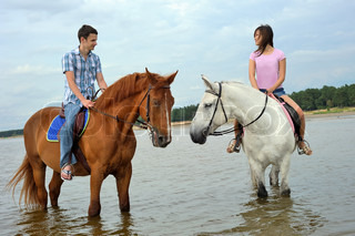 Man and a woman in the sea on horseback