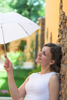 Young girl is giding from sun with white umbrella