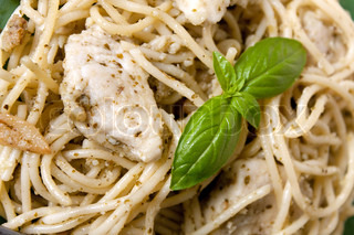 A dish of spaghetti with pesto garlic and chicken with a basil leaf garnish