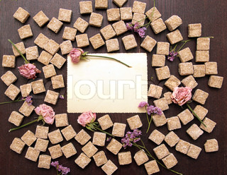 frame of sweet dreams on wooden background: flower, sugar and pl