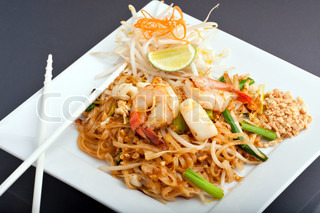 Seafood pad Thai dish of Thai fried rice noodles on a square white plate with chopsticks and grated carrot garnish