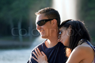 A happy young couple in their mid 20s wearing sunglasses with the girl leaning on the guys shoulder