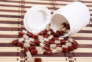 Brown capsules with granular medicine on a mat background