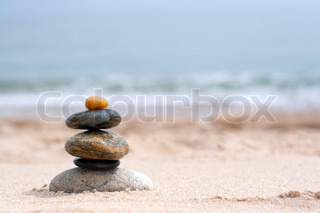 A pile of round smooth zen rocks stacked in the sand at the beach