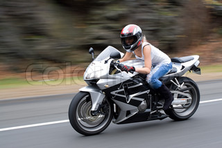 Abstract blur of a pretty girl driving a motorcycle at highway speeds