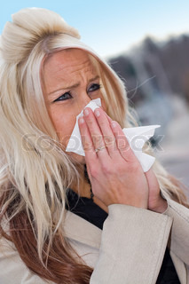 This young woman sneezing into a tissue either has a cold or really bad allergies