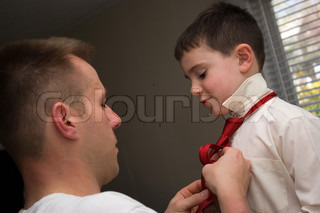 A young dad helps his son get ready by helping him tie his neck tie