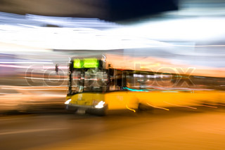The yellow bus quickly goes on an evening city
