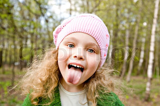 Cheerful little girl in a pink cap puts out the tongue in forest