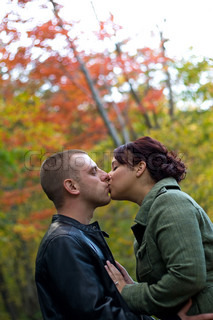 A young happy couple passionately kissing each other outdoors during fall or autumn