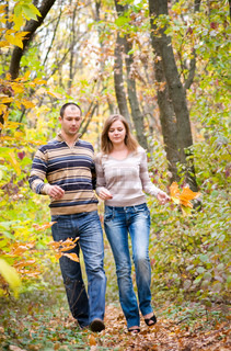 happy couple walking in autumn forest